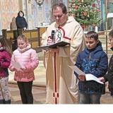 Kaplan Marco Stangl stellte beim Gottesdienst die diesjährigen Kommunionkinder vor. −Foto: Baierl